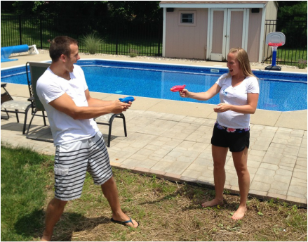 Pool party gender reveal with squirt guns filled with pink or blue paint
